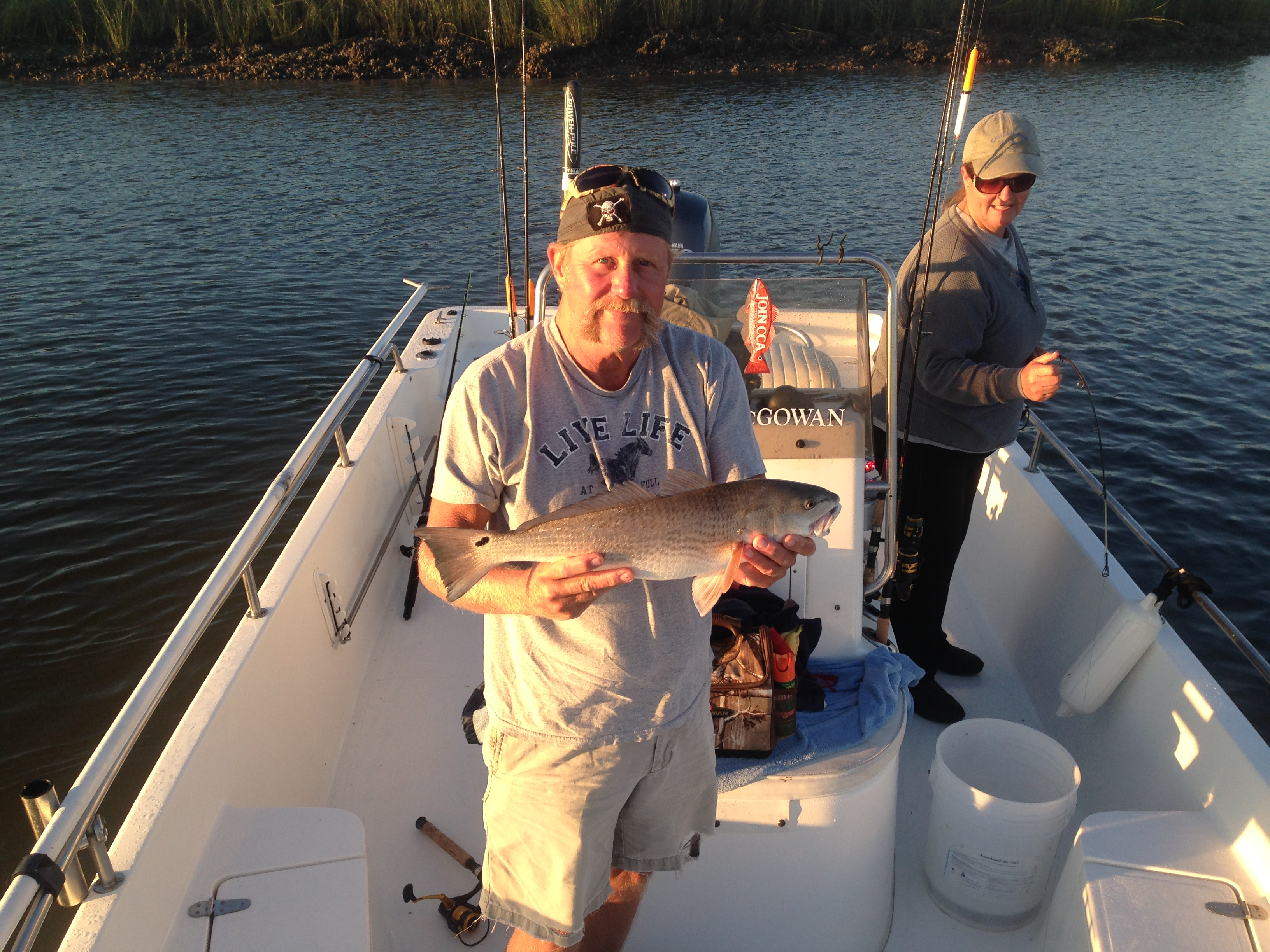 Mike Savage with a nice redfish! Angela is in the background with her red on the deck of the boat! Good fishing!