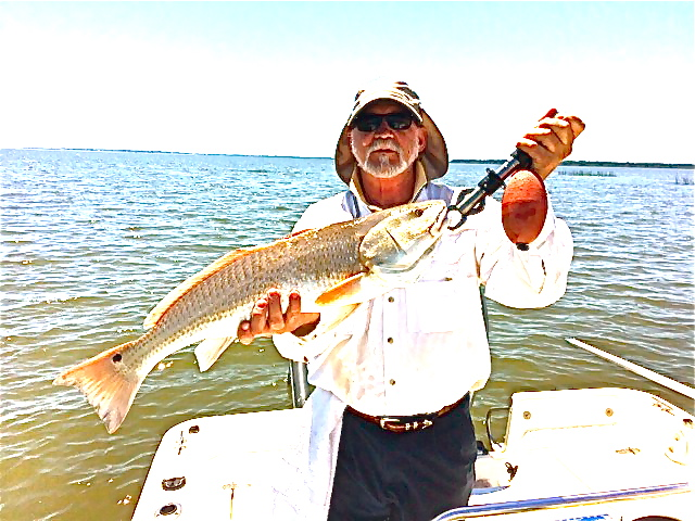 "A nice day catching with Bill Johnston and Alex Cathy! Alex is shown here with 28"" red! Redfish bite is on! Fish On!"