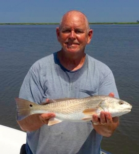 Capt Jack with a nice schoolie redfish.