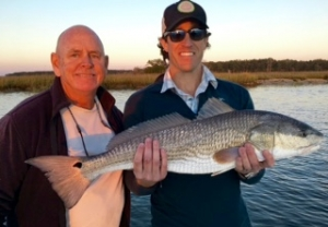 JT landing a nice inshore red! Capt. Jack is to JT's right.